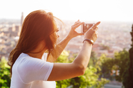 Italy, Verona, Italy, Verona, redheaded woman taking photo with smartphone by sunset - GIOF04218