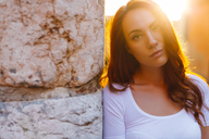 Portrait of redheaded woman leaning against wall at sunset - GIOF04221