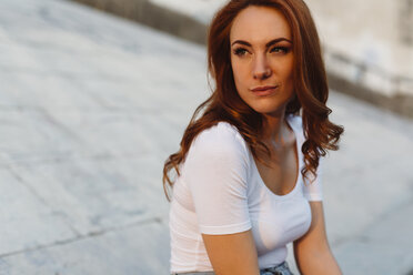 Portrait of redheaded young woman using cell phone outdoorsat sunset - GIOF04224