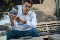 Mature businessman sitting in coffee shop, checking time - GUSF00980