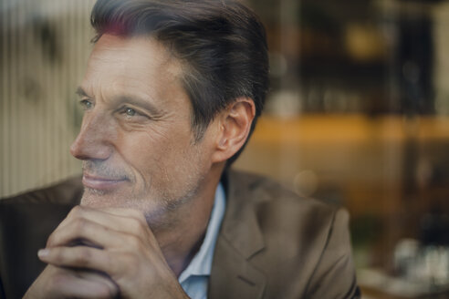 Mature businessman sitting in coffee shop, looking out of window - GUSF00983