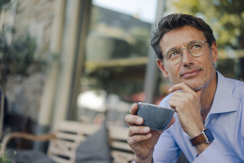 Mature businessman sitting in coffee shop, drinking coffee - GUSF00986
