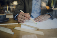 Mature businessman sitting in coffee shop, drawing on paper - GUSF00992