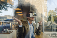 Mature businessman sitting in coffee shop, looking through VR glasses - GUSF00995