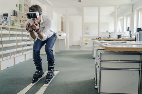 Businessman skiing in office, using VR glasses - GUSF00998