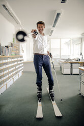 Businessman skiing in office, pointing with ski pole - GUSF01007