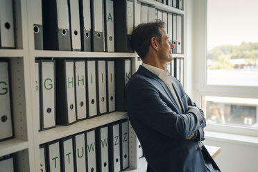 Businessman in company archive, leaning against shelf with files - GUSF01010