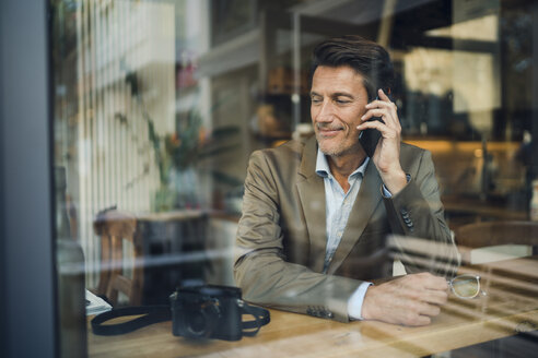 Mature businessman sitting in coffee shop, talking on the phone - GUSF01031