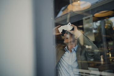 Mature businessman sitting in coffee shop, looking through VR glasses - GUSF01034