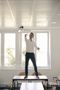 Businessman playing with inflatable airplane in office - GUSF01049