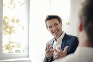Successful businessman talking to colleague - GUSF01055