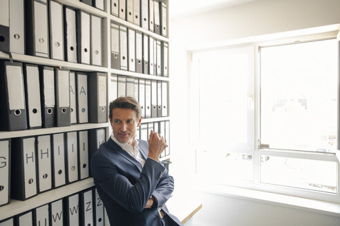 Businessman in company archive, leaning against shelf with files - GUSF01070