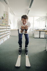 Businessman skiing in office - GUSF01085