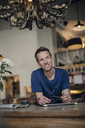 Mid adult man sitting in coffee shop, smiling - GUSF01094