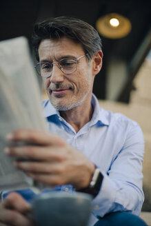 Businessman sitting in coffee shop, reading newspaper, drinking coffee - GUSF01106