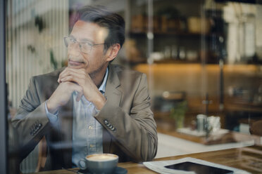 Mature businessman sitting in coffee shop, smiling - GUSF01109