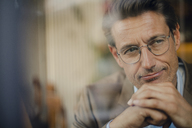 Mature businessman sitting in coffee shop, looking out of window - GUSF01112