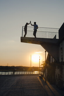 Two friends high-fiving at sunset, standing on observation platform - GUSF01121