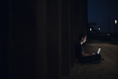 Mid adult man sitting cross-legged on ground, using laptop at night - GUSF01127