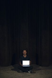Mid adult man sitting cross-legged on ground, showing blank laptop screen - GUSF01130