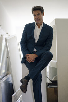 Redundant businessman sitting in storage room - GUSF01133