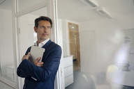 Successful businessman standing in office with laptop - GUSF01145