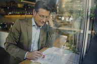 Mature businessman sitting in coffee shop, drawing outline of a house - GUSF01160