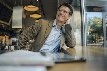 Mature businessman sitting in coffee shop, smiling - GUSF01172