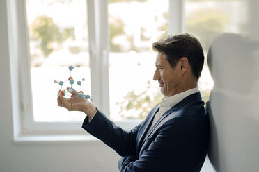 Successful businessman leaning on whiteboard, holding molecule model - GUSF01181