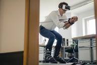 Businessman skiing in office, using VR glasses - GUSF01187