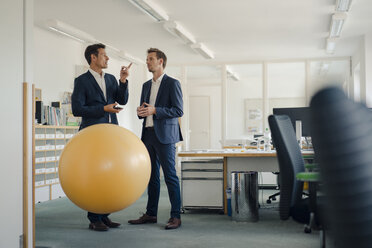 Two businessman checking smartphone with yellow fitness  ball in foreground - GUSF01193