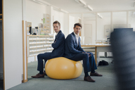 Two businessman checking smartphone with yellow fitness  ball in foreground - GUSF01196