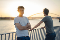 Two friends watching sunset at the river - GUSF01205