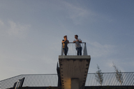 Two friends standing on observation platform, talking - GUSF01211