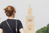 Morocco, Marrakesh, back view of woman looking at minaret of Koutoubia mosque - MMAF00487