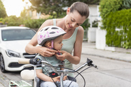 Mother and daughter, daughter wearing helmet sitting in children's seat - DIGF04955