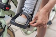 Child sitting in children's seat, mother fastening safety belt - DIGF04961