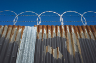 Low angle view of worn corrugated metal fence, razor wire above. - MINF08681