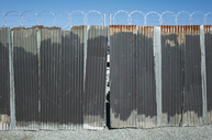 Worn corrugated metal fence, razor wire above. - MINF08684