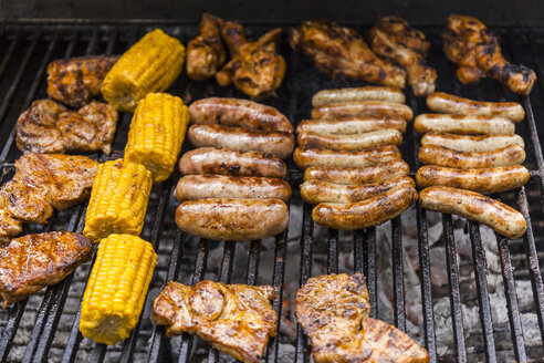Different meat, maize and fried sausages on barbecue grill - TCF05636
