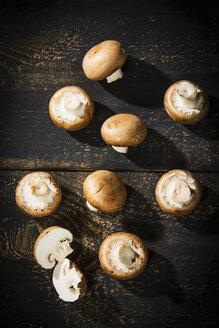 Sliced and whole Crimini Mushrooms on dark wood - MAEF12705