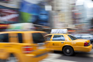 Yellow cabs driving on street near Times Square in Manhattan, New York, USA, motion blur. - MINF08895