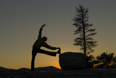 A young woman does yoga in the evening light. - AURF00702