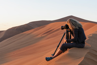 Africa, Namibia, Namib desert, Naukluft National Park, female photograper photographing at early morning light, sitting on sand dune - FOF10066