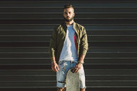 Portrait of young man with skateboard - RAEF02108