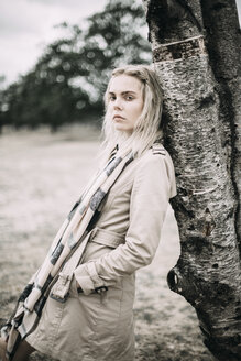 Portrait of fashionable young woman wearing coat and scarf leaning against tree trunk - JESF00082
