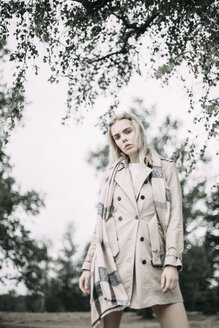 Portrait of fashionable young woman wearing coat and scarf in nature - JESF00085
