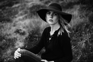 Portrait of young woman wearing black hat sitting on a meadow - JESF00091