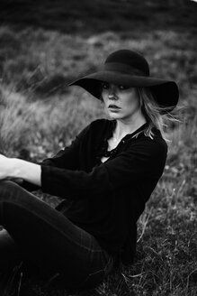 Portrait of young woman wearing black hat sitting on a meadow - JESF00094