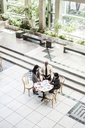 Mixed race group of three people in an informal meeting around a table in a lobby area. - MINF08937